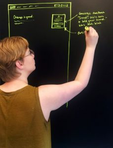 UX/UI designer, Lacie Webb, drawing wireframes on a blackboard
